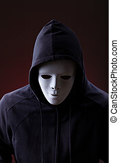 Man wearing mask - Man in hood wearing mask over dark...