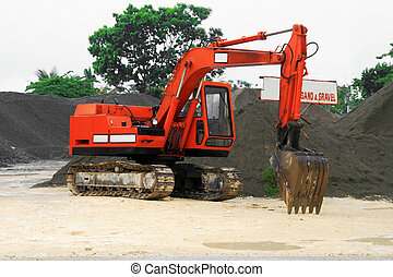 orange back hoe - an orange back hoe parked near a heap of...