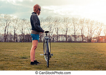 Young woman standing in park with bicycle