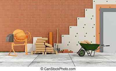 Construction site with concrete mixer, wheelbarrow, bags of...