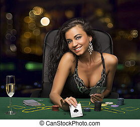 brunette girl in the casino playing poker, shows a playing...