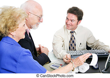 Tax Time With Accountant - Senior couple going over their...