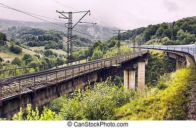 Railway bridge - Train crossing an old iron and stone...