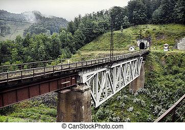 Railway bridge - Train crossing an old iron and stone...