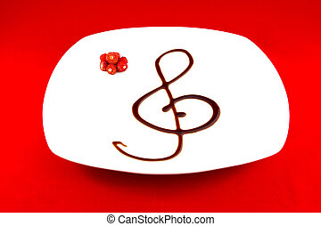 Treble clef made ??with balsamic vinegar on white plate with...