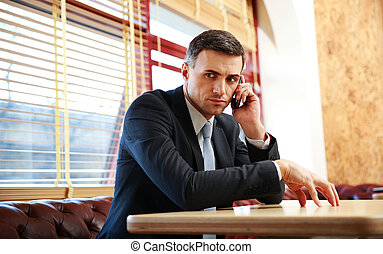 Pensive businessman sitting and talking on the phone at...