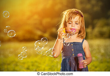 little girl blowing soap bubbles in nature - little girl...