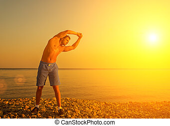 man athlete practicing, playing sports and yoga on the beach at sunset