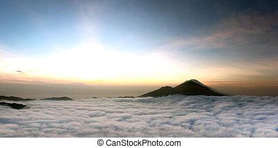 Sunrise above clouds with a mountain volcano view. Mt. Batur...