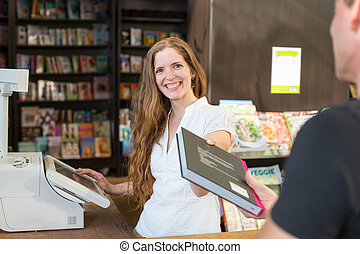 Cashier in bookstore serving a customer or client - Female...