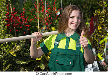 Farmer or gardener posing with shovel in garden nursery