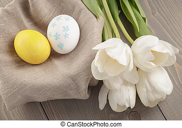 pastel color easter eggs with tulips on table, slightly...