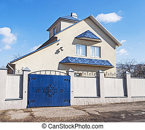 New country house with blue roof, sunny spring day