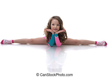 Smiling curly gymnast sitting on splits, isolated over white...