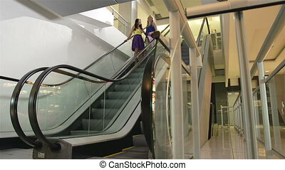 Happy Time - Ladies descending on escalator while doing...