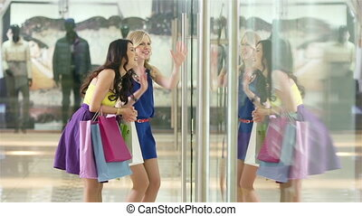 Shopping excitement - Charming girls discussing new gorgeous...
