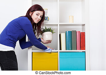 Young woman during dusting furniture at home