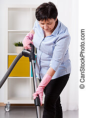 Woman during hoovering - Woman holding vacuum cleaner during...