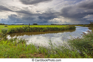 River with Dramatic Clouds In Friesland, Netherlands -...