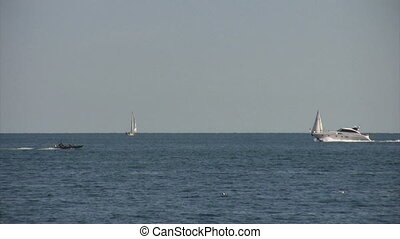 boating - speedboats pass sailboats on lake