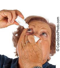 Elderly woman applying eye drops