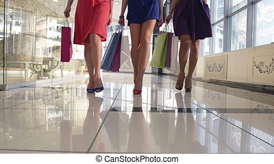 Legs of shoppers - Legs of shopaholics with shopping bags...