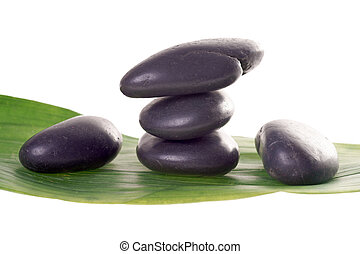 Hot Stones with green leaf over a white background