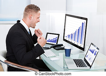 Businessman celebrating a performance graph sitting at his...