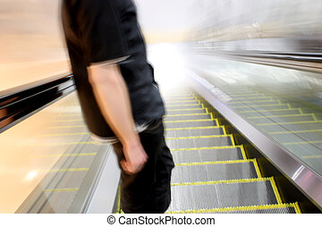 Escalator Toward the Light - Man descending an escalator...