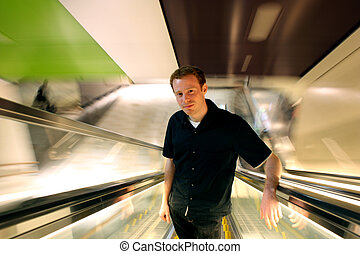 Calm Man - Happy man in 20s ascending an escalator with...