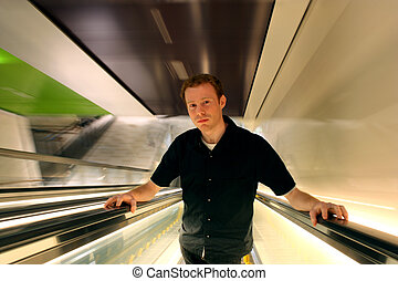 Serene Modern Man - Man in 20s ascending an escalator,...