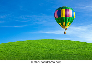 Hot air balloon flying over green field