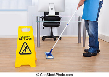 Warning notice as a janitor mops the floor - Yellow warning...