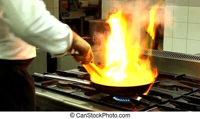 flame in a pan cook preparing food - CHEF AND FIRE IN THE...