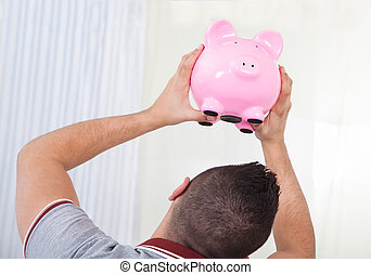 Rear view of young man checking out piggy bank at home