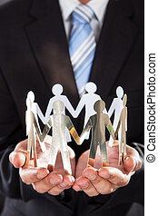 Businessman Holding Metal Team In Cupped Hands - Midsection...