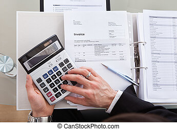 Cropped Image Of Businessman Calculating Invoice At Desk -...