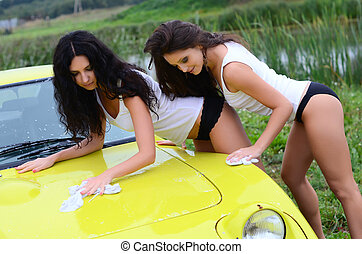 The beautiful woman washes the car - The two beautiful woman...