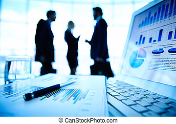 Business information - Laptop and financial document with...