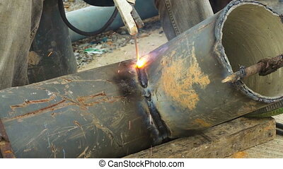 Welder uses arc welding pipe metal on site in outdoor.
