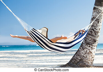 Woman Stretching In Hammock At Beach - Happy young woman...