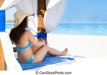 Woman Relaxing In Gazebo At Beach - Full length side view of...