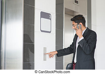 Indian businessman entering elevator - Asian Indian...