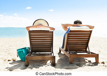 Couple relaxing on deck chairs at beach resort - Rear view...