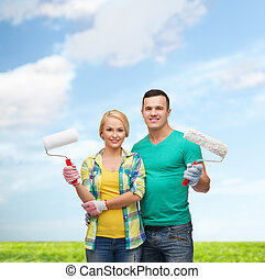 smiling couple in gloves with paint rollers - repair,...