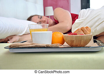 woman sleeping on her bed with a breakfast