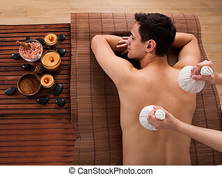 Young Man Receiving Massage With Stamps In Spa - High angle...