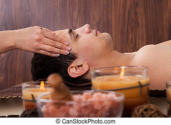 Man Receiving Head Massage From Massager In Spa - Side view...