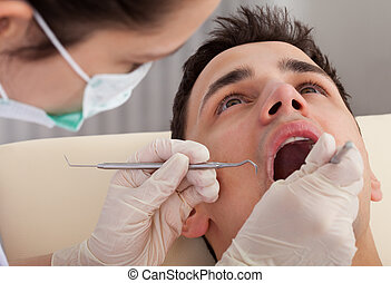 Cropped Image Of Dentist Examining Patient's Mouth - Cropped...