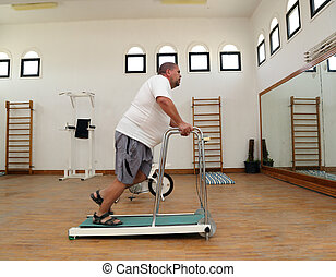 overweight man running on trainer treadmill - fitness -...